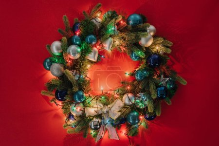 top view of christmas wreath decorated with toys and lights on red background