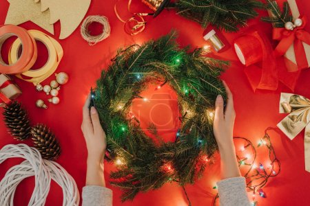 partial view of woman holding handmade christmas wreath with lights on red background