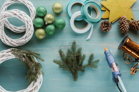 flat lay with christmas balls, pine tree branches and glue gun for handmade christmas wreath