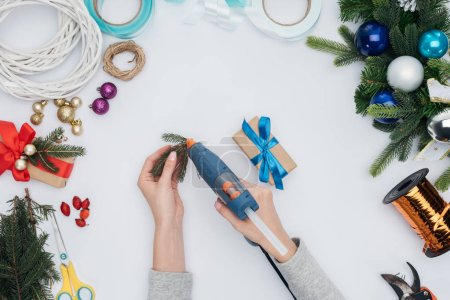 partial view of woman decorating christmas present with pine tree branch isolated on white