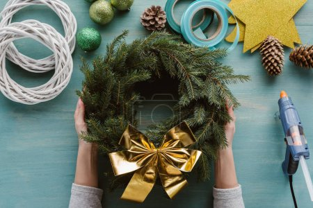 cropped shot of woman holding handmade pine tree wreath with golden bow and decorations on blue wooden tabletop