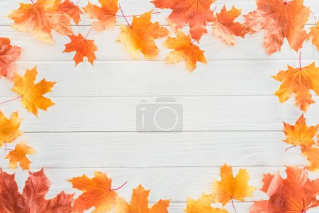 top view of frame of orange autumnal maple leaves on wooden surface