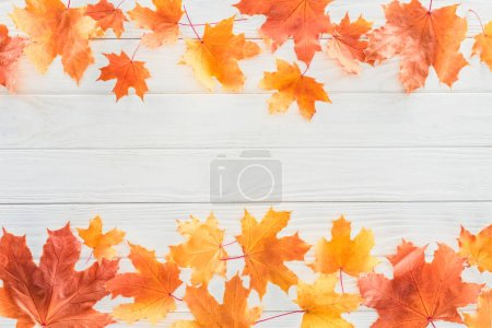 Photo for Elevated view of orange autumnal maple leaves on wooden surface - Royalty Free Image