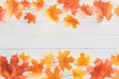 elevated view of orange autumnal maple leaves on wooden surface