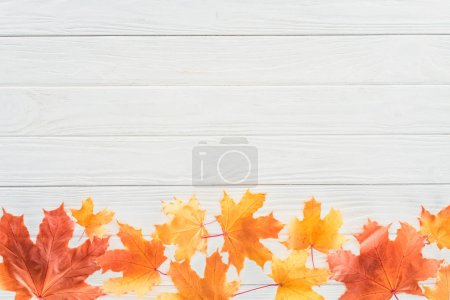 top view of autumnal fallen maple leaves on wooden table