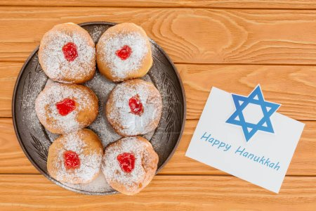 top view of sweet donuts and happy hannukah card on wooden tabletop, hannukah celebration concept