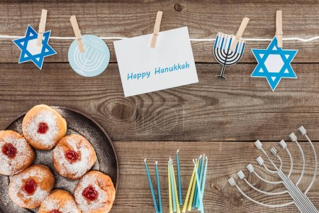 flat lay with doughnuts, candles, menorah and happy hannukah card on wooden surface, hannukah concept