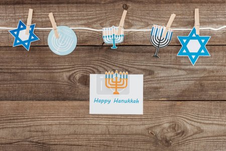 flat lay with happy hannukah card and holiday paper signs pegged on rope on wooden tabletop, hannukah concept