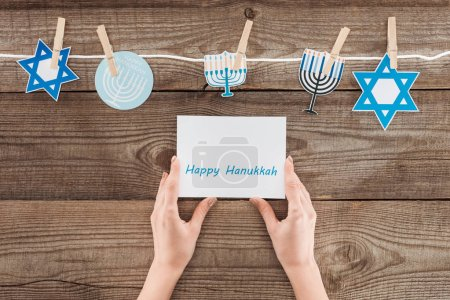 cropped shot of woman holding happy hannukah card with holiday paper signs peged on rope on wooden surface, hannukah concept