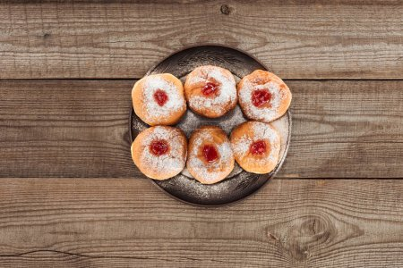 top view of sweet donuts on wooden tabletop, hannukah celebration concept