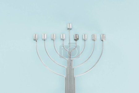 top view of traditional menorah on blue backdrop, hannukah celebration concept