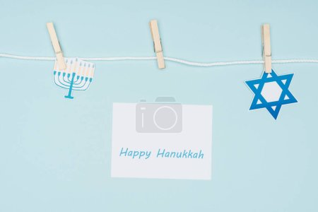 top view of happy hannukah card and holiday paper signs pegged on rope isolated on blue, hannukah concept