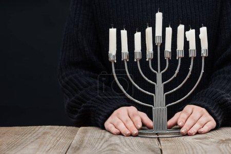 photo recadrée de femme debout au dessus de table en bois avec la menorah et bougies sur fond noir, concept de fête de Hanouka