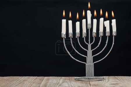 Photo for Close up view of jewish menorah with candles for hannukah holiday celebration on wooden tabletop isolated on black, hannukah concept - Royalty Free Image