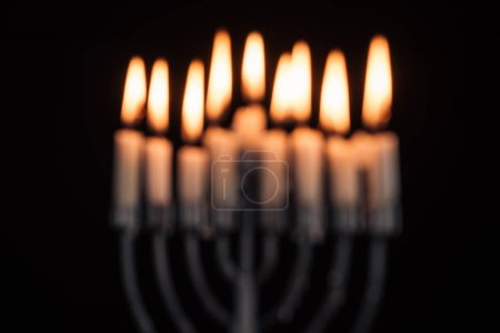 defocused picture of jewish menorah with candles for hannukah holiday celebration isolated on black, hannukah concept