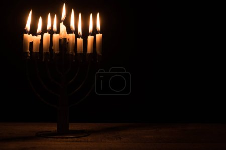 close up view of menorah with candles for hannukah holiday celebration on wooden tabletop on black background, hannukah concept