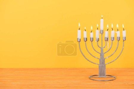 Photo pour Vue rapprochée de menorah avec des bougies pour la célébration des vacances hannukah sur plateau en bois isolé sur jaune, concept hannukah - image libre de droit
