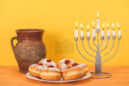 close up view of sweet doughnuts, clay jug and menorah on wooden surface on yellow backdrop, hannukah concept