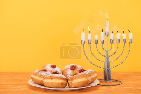 close up view of sweet doughnuts and menorah with candles on wooden surface isolated on yellow, hannukah concept