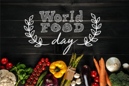 Photo for Different fresh vegetables lying in row on wooden tabletop with world food day inscription - Royalty Free Image