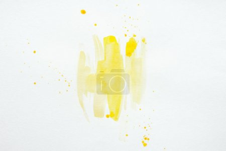 abstract yellow watercolor splatters on white paper background