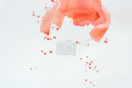 abstract red watercolor splatters on white paper