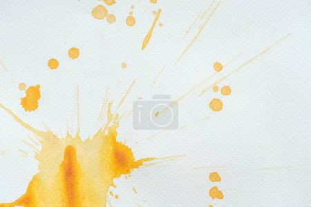 artistic orange watercolor splatters and blots on white paper