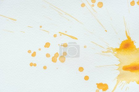 abstract orange watercolor splatters and blots on white paper