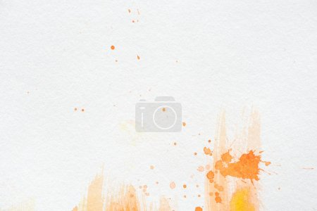 orange watercolor painting with splatters on white paper