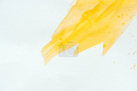 abstract background with yellow watercolor strokes on white paper