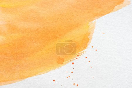 abstract orange watercolor painting with paint blots on white paper