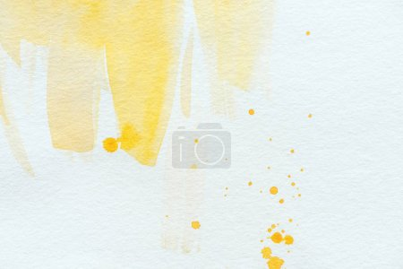 yellow watercolor strokes and splatters on white paper background