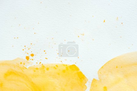 artistic yellow watercolor splatters on white paper background