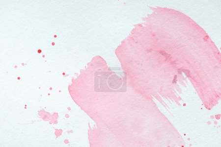 creative background with pink watercolor strokes and splatters on white paper