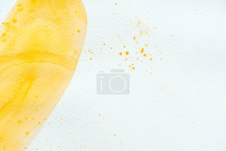 abstract yellow watercolor stroke and splatters on white paper background