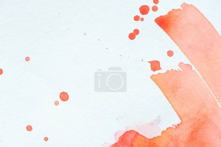 creative background with red watercolor strokes and splatters on white paper