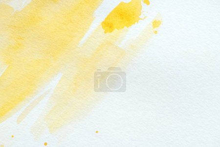 abstract yellow watercolor strokes on white paper