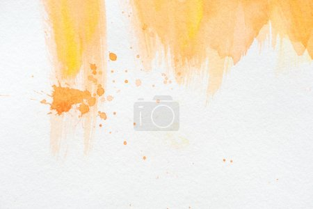 abstract orange watercolor painting with splatters on white paper
