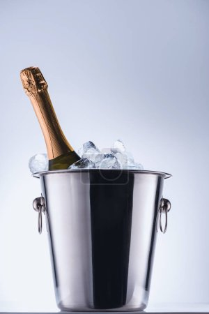 close up view of bottle of champagne in bucket with ice cubes on grey background