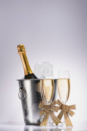 close up view of bottle of champagne in bucket and glasses of champagne on grey backdrop