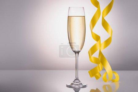 bouchent la vue du verre de confettis champagne et jaune sur fond gris