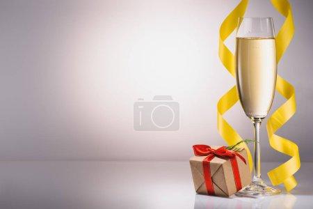 bouchent la vue de verre de champagne et cadeau enveloppé de Noël sur fond gris