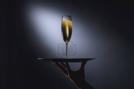 partial view of waitress holding serving tray with glass of champagne on dark background