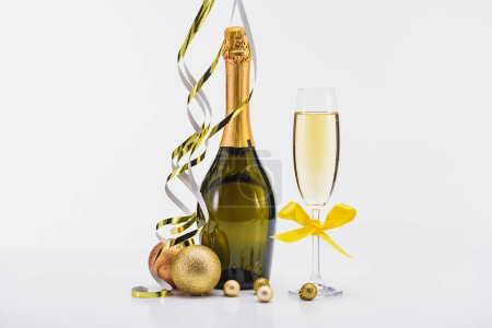 Photo for Close up view of bottle and glass of champagne, confetti and christmas toys on white backdrop - Royalty Free Image
