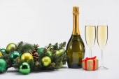 close up view of bottle and glasses of champagne, christmas wreath and gift on white background