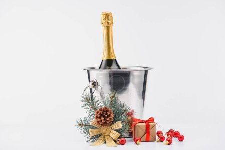 close up view of bottle of champagne in bucket, christmas toys and wrapped gift on grey backdrop