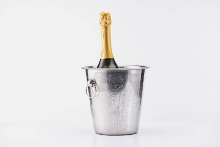 close up view of bottle of champagne in bucket on grey backdrop
