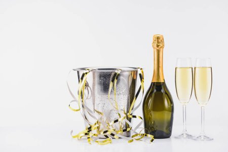 Photo for Close up view of bucket with confetti, bottle and glasses of champagne on grey backdrop - Royalty Free Image
