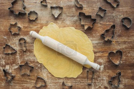Photo for Flat lay with raw dough, rolling pin and cookie cutters arranged on wooden tabletop - Royalty Free Image