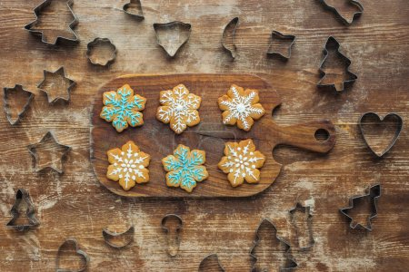 Photo for Flat lay with christmas cookies on cutting board and cookie cutters around on wooden surface - Royalty Free Image
